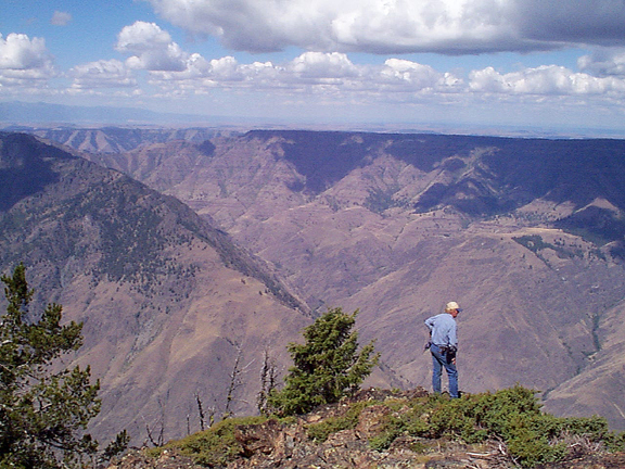 A man looks over the side of the Hells Canyon rim down into the desert valley below.